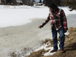 Brand Debungee brother of deceased Stacey DeBungee pointing at the spot where his brother was found in the McIntyre River